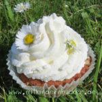 Muffin mit Sahne und Gänseblümchen