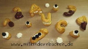 Buchstaben und Zahlen aus Brandteig mit Sahne, Schokolade und Brombeeren zum Schulanfang